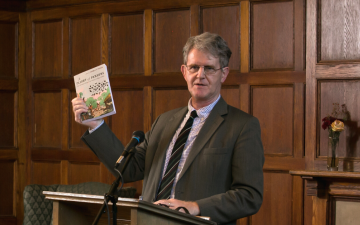 Thomas Power holding a book he authored