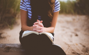 Woman praying with open Bible on her lap