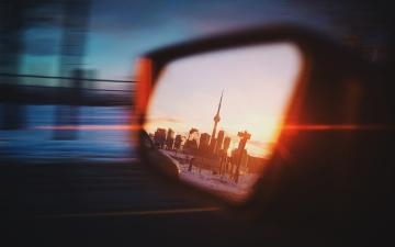 Toronto's cityscape reflected in a side mirror of a car (photo credit: Daniel Novykov - Unsplash)
