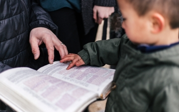 Boy touches Bible by Priscilla Du Preez unsplash