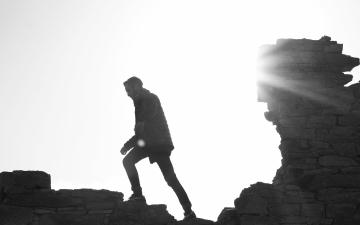 Silhouette of man walking on a broken wall