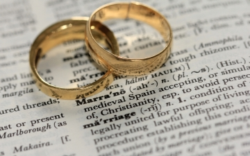 two gold rings on a dictionary page defining the word marriage