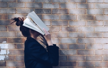 Young woman holding textbook over her face