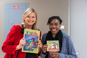 Two participants holding a children book and a CD respectively