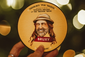 A coaster with an illustration of Bruxy Cavey