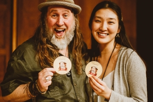 Bruxy Cavey and Joyce Shin, holding the Bruxy coasters designed by Joyce