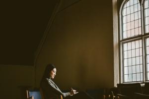 Joyce Chin facing a window in Sheraton Hall, Wycliffe College